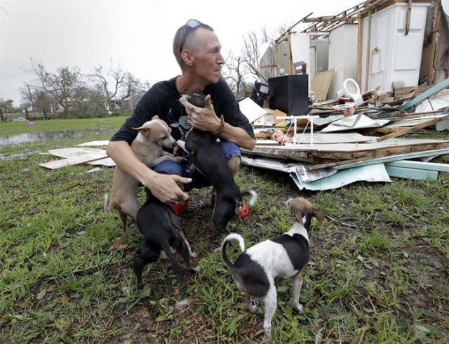 man w pets in destroyed home