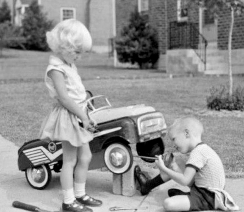 A young auto mechanic fixing a little girls vehicle in the 1950s
