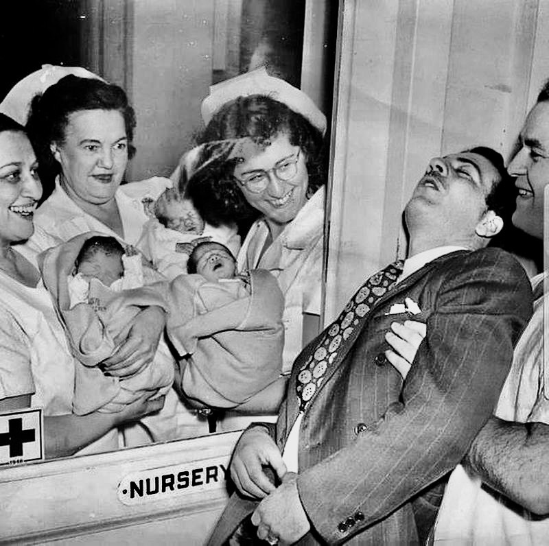 Nurses showing a set of triplets to their surprised father in a New York hospital 1946