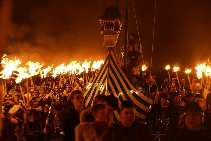 Guizers dressed as Vikings from the Jarl Squad gather around the longship with burning torches.