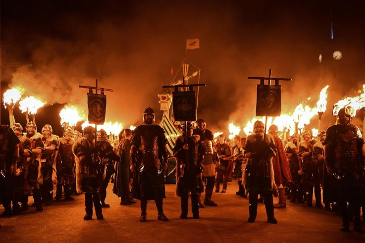 Guizers dressed as Vikings from the Jarl Squad march toward the longship with burning torches