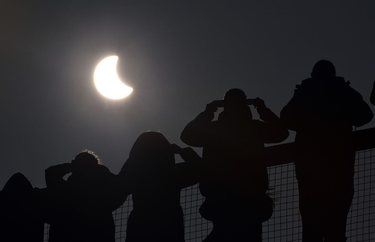 people with glasses seeing the moon covering sun