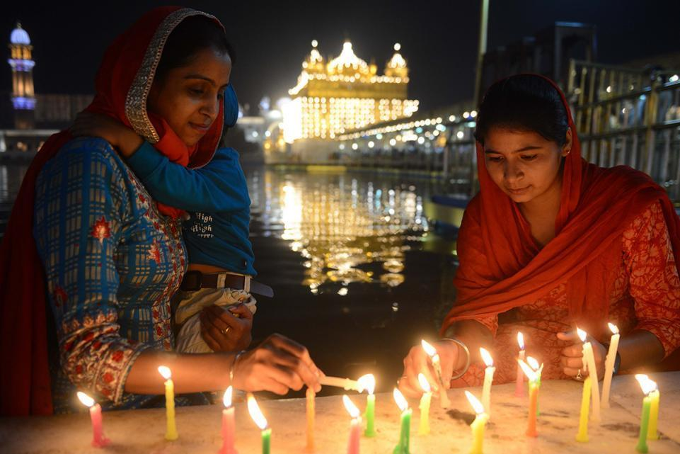 India Sikh devotees light candles