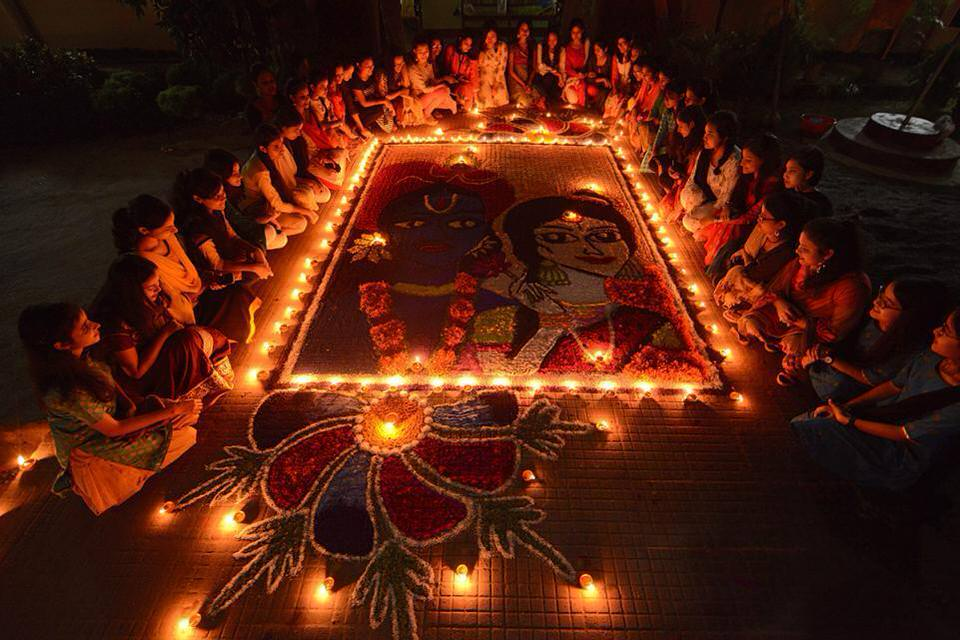 Indian girls light earthen lamps on a Rangoli in Guwahati. 1